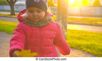 Adorable happy baby girl holding yellow leaf and show it to...