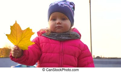 Adorable happy baby girl with yellow leaf in autumn