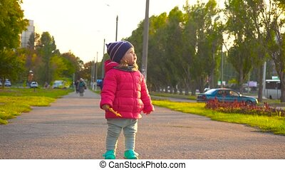 Adorable happy baby girl with yellow leaf in city - Adorable...