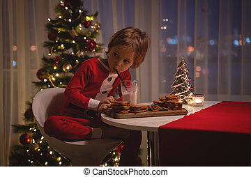 adorable happy boy in santa hat holding baking tray with ginger cookies and smiling at camera
