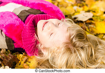 adorable happy child in autumn leaves