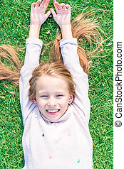 Adorable happy girl on green grass