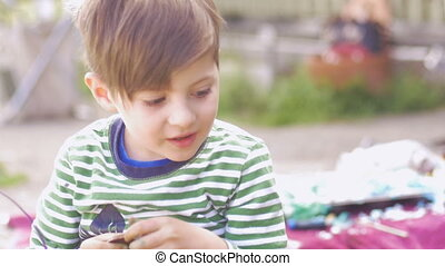 Adorable happy little boy eating chocolate outside in slow...