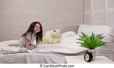 adorable happy little child girl playing with teddy bear