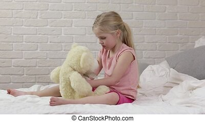 adorable happy little child girl playing with teddy bear in...