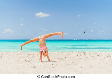 Adorable happy little girl have fun on beach vacation