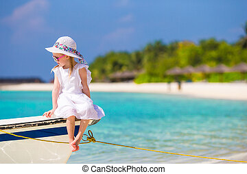 Adorable happy little girl in hat on beach vacation