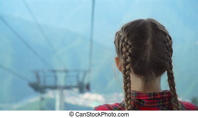 Adorable happy little girl in the cabin on the cable car in...