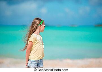 Adorable happy little girl on white beach