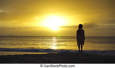 Adorable happy little girl on white beach at sunset. Silhouette of little girl on the coast on a beautiful sunset