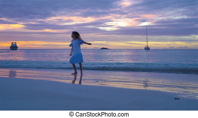 Adorable happy little girl on white beach at sunset....