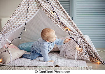 Adorable infant boy playing with kids tent in cozy blue playroom