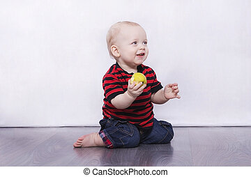 Adorable infant boy sitting on the grey floor with apple