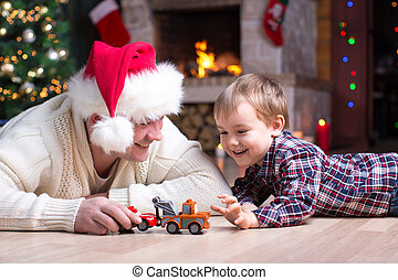Adorable kid boy and father playing with cars toys at home in christmastime. Happy child having fun with gifts. Colorful christmas lights on background. Family and holiday lifestyle concept.