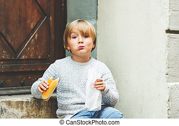 Adorable kid boy eating salami sandwich outside
