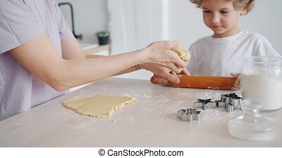 Adorable kid cooking pastry with mother holding dough...