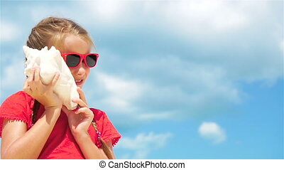 Adorable kid listening a big seashell on white tropical beach. SLOW MOTION