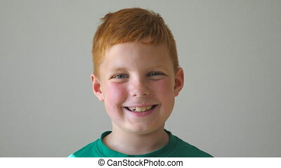 Adorable kid looking into camera with joyful smile indoor. Portrait of happy red-haired boy with freckles inside. Close up emotions of handsome male child with glad expression on face. Slow motion.