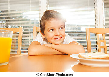 Adorable kid sitting in the kitchen at breakfast