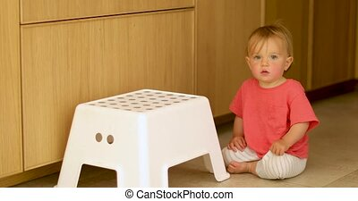 Adorable kid sitting on floor with white chair - Cute...