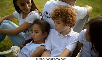 Adorable kids having rest after working with volunteers -...