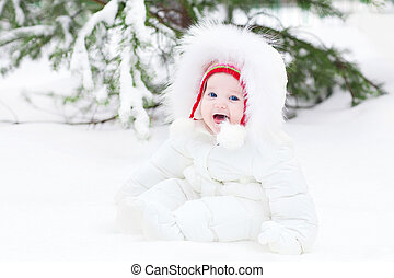 Adorable laughing baby sitting in snow under a Christmas tree