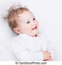 Adorable laughing little baby wearing a warm knitted jacket on a
