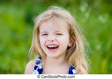 Adorable laughing little girl with long blond curly hair