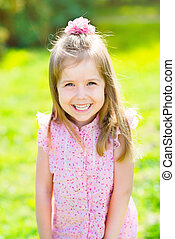 Adorable laughing little girl with long blond hair