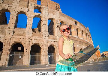 Adorable little active girl with map in front of Colosseum in Rome, Italy. Kid spending childhood in Europe