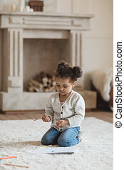 adorable little african american girl drawing with pencils and sitting on carpet at home