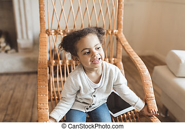 adorable little african american girl with digital tablet and sitting on rocking chair at home