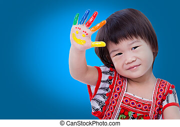 Adorable little asian (thai) girl painting her palm, on blue...