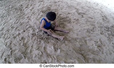 Adorable Little baby boy playing sand on white beach