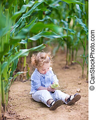 Adorable little baby girl with curly hair sitting in a field pla