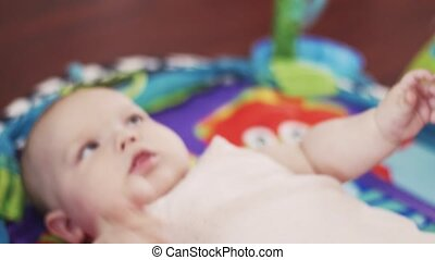 Adorable little baby lie on rug playing with hanging toys. Cute. Motherhood