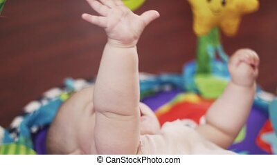 Adorable little baby lie on rug touching toys by hands. Cute. Motherhood. Child