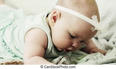 Adorable little baby lie on sofa put baby dummy in mouth....