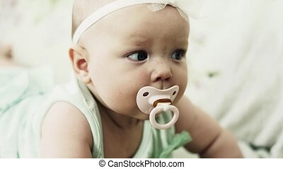 Adorable little baby lie on sofa with baby dummy. Cute girl. Looking in camera.