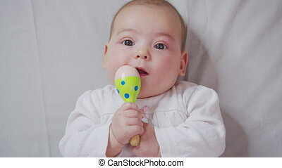 Adorable little baby playing a toy on bed.