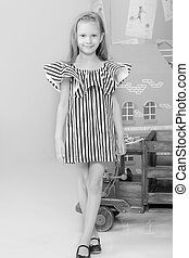 Adorable little blond girl in very short summer striped dress.