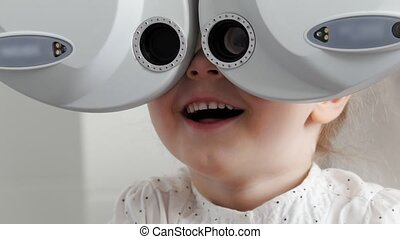 Adorable little blonde girl checks eyesight at ophthalmology...