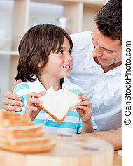 Adorable little boy and his father eating bread