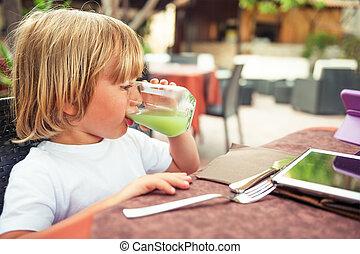 Adorable little boy drinking fresh apple juice in a restaurant