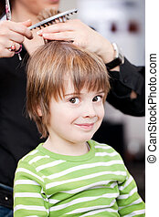 Adorable little boy getting a hair cut by a professional...