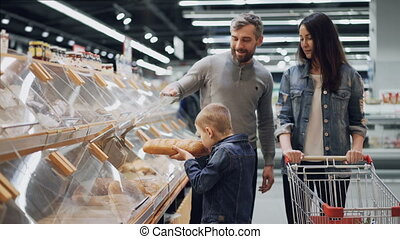 Adorable little boy is helping his parents to choose bread in bakery department in food store, he is taking loaf and smelling it then putting in cart.