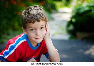 adorable little boy looking at the camera with a shy smile...