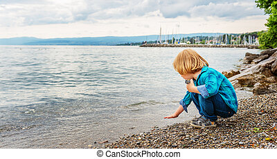 Adorable little boy of 3-4 years old playing by the lake on a nice day