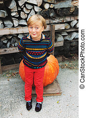 Adorable little boy of 5-6 year old with funny expression on his face choosing halloween pumpkin on farm market