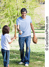 Adorable little boy playing baseball with his father